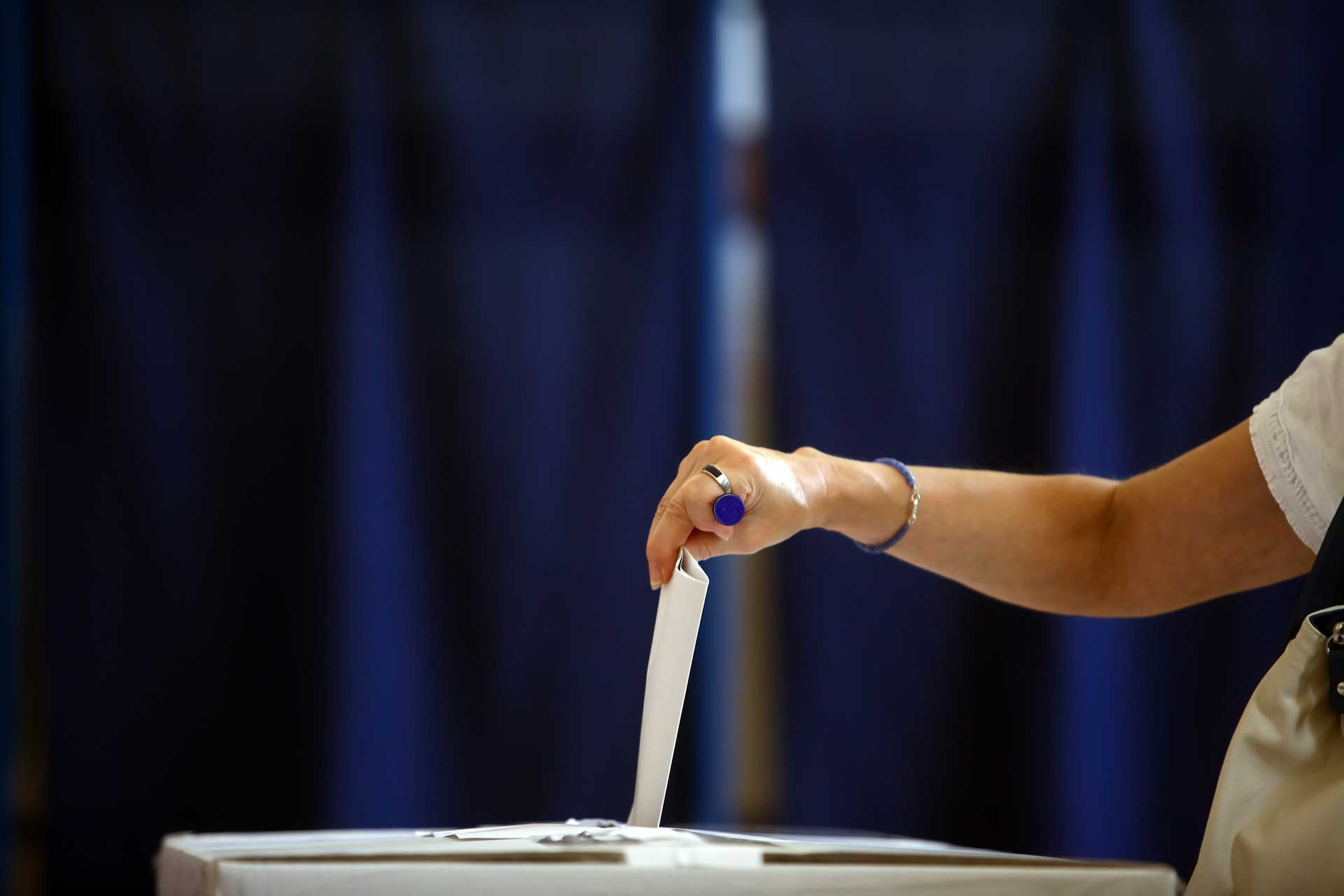 hand slipping paper ballot into ballot box