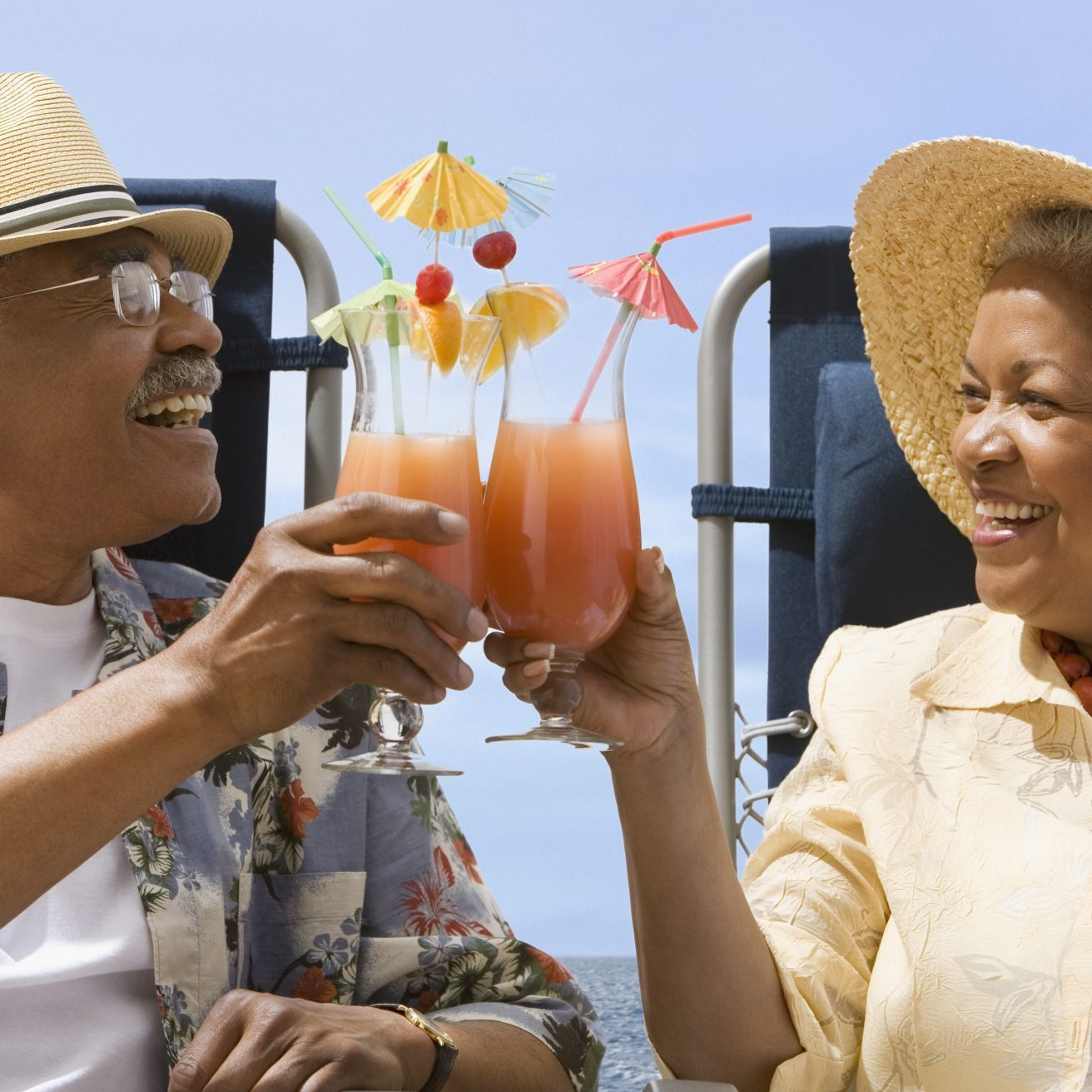 African american couple sharing drinks on beach