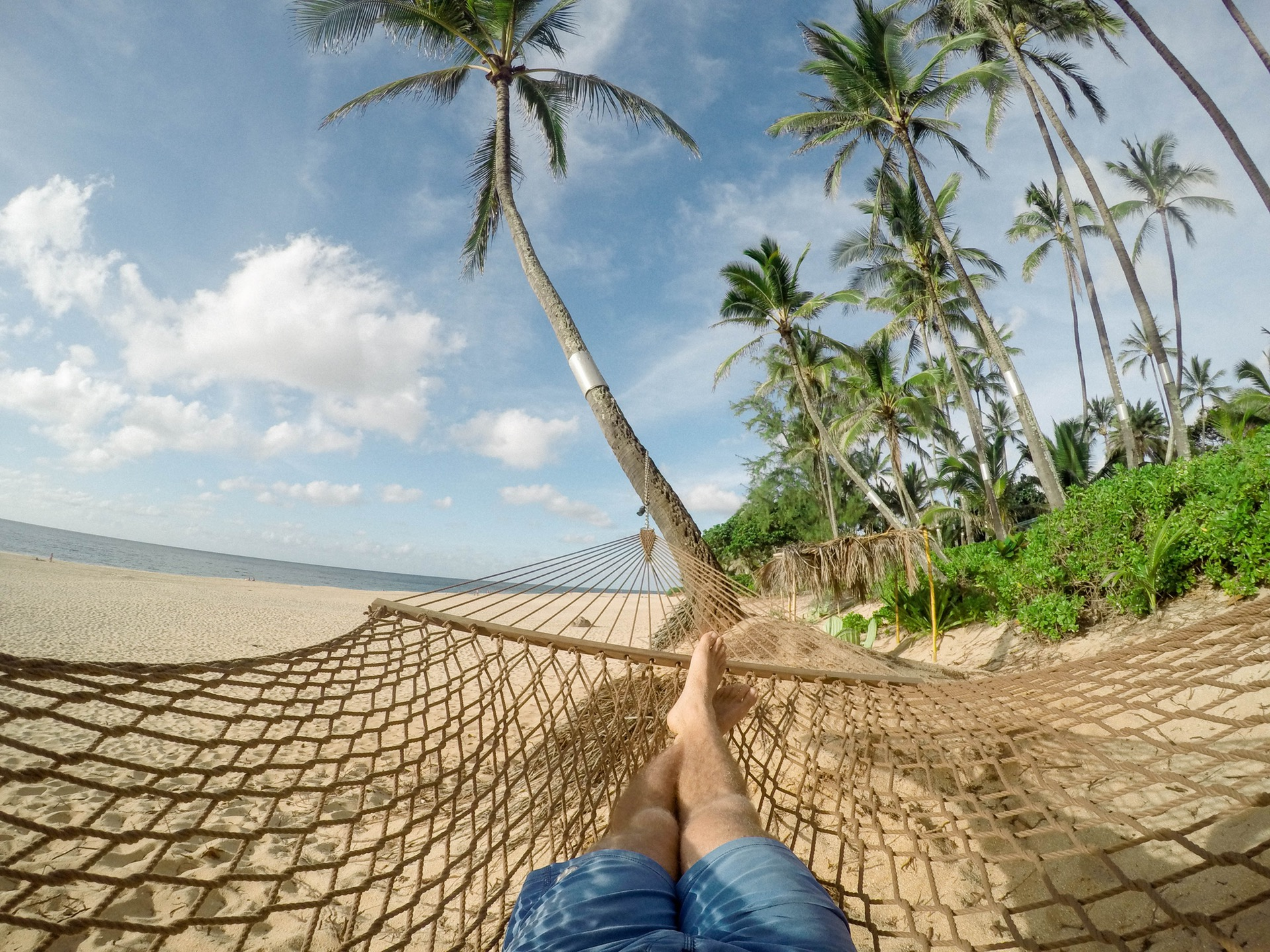 Point of view shot of man laying on hammock on beach